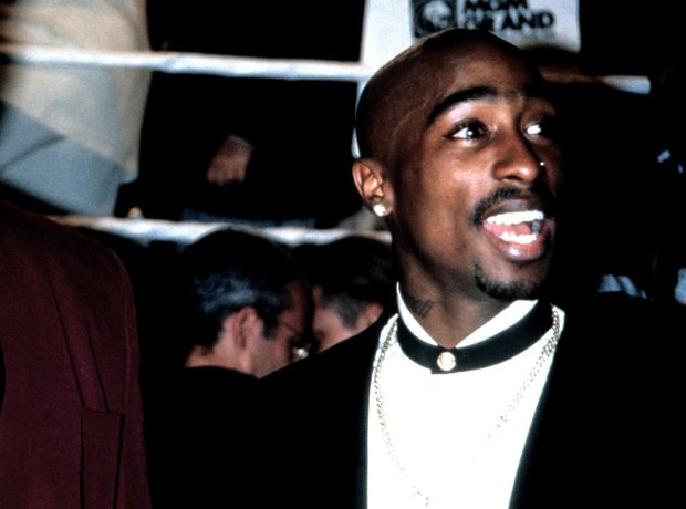 Tupac Shakur next to a boxing ring wearing a suit