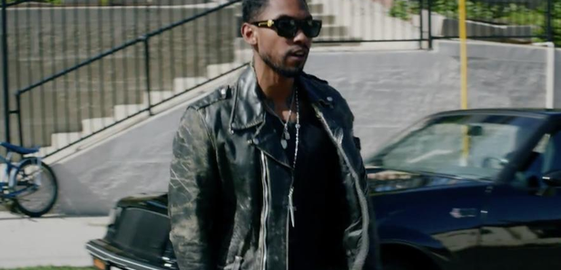 Miguel walking down the street in music video